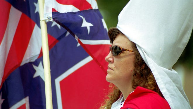 A female member of the Ku Klux Klan stands at attention near a hybrid flag she created from the American and Confederate flags at a KKK rally on the steps of the Elwood (Ind.) City Building on Aug. 25, 2001. The Klan held a 45-minute rally attended by hundreds of  pro- and anti-Klan spectators who remained mostly peaceful.