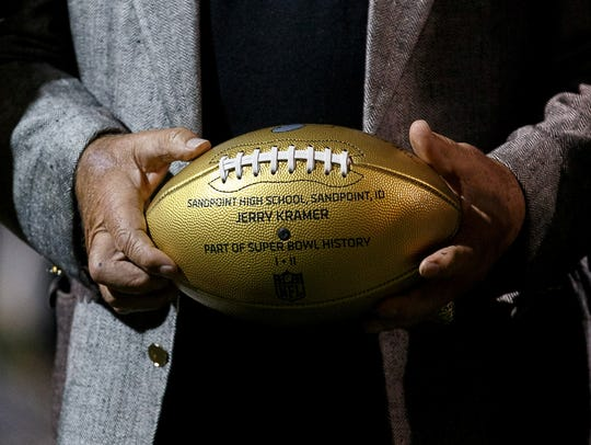 A close-up of the NFL 50 golden ball, held by former