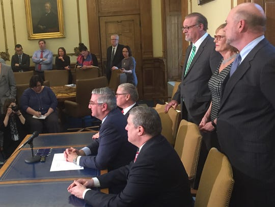 Gov. Eric Holcomb (seated, center) signs a bill Wednesday