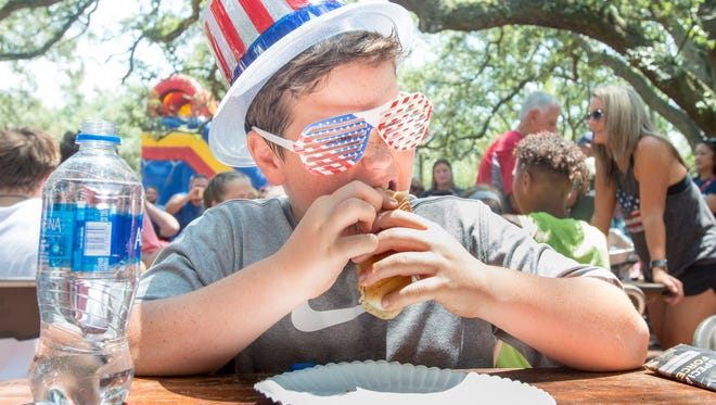 Evan Richardson, 11, of Pensacola, concentrates during the hot dog eating contest as part of the Sertoma's Independence Day Celebration at Seville Square in Pensacola on Wednesday, July 4, 2018.