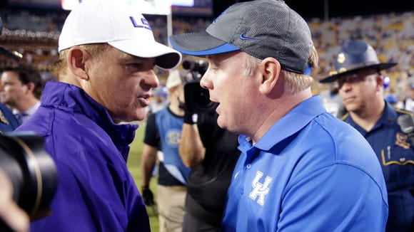 LSU head coach Les Miles talks with Kentucky head coach Mark Stoops after their NCAA college football game in Baton Rouge, La., Saturday, Oct. 18, 2014. LSU won 41-3. (AP Photo/Gerald Herbert)