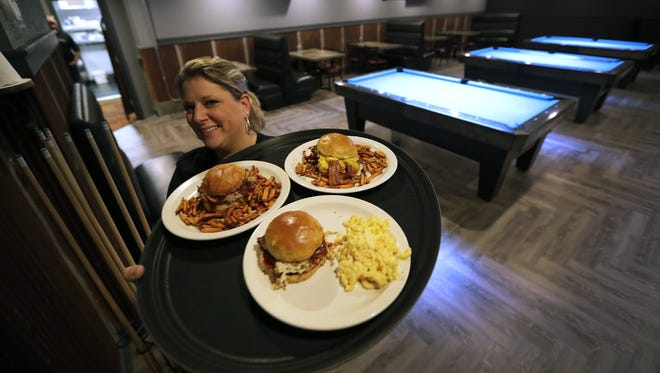 Jennifer Wollin delivers food to diners as she passes through the pool hall area at Mad Apple Burger & Billiard Co., in Grand Chute.
