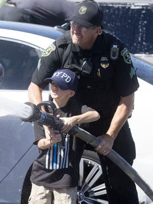 Glendale police Sgt. Jeff Turney and Caleb Benedetto, 7, of Avondale, participate in a benefit car wash for fallen Officer David Glasser.