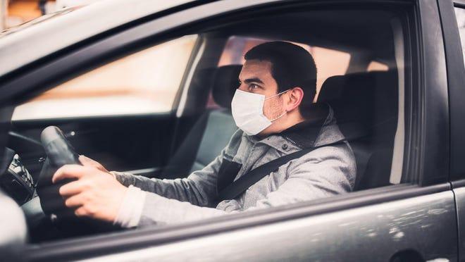 Man wearing mask driving car