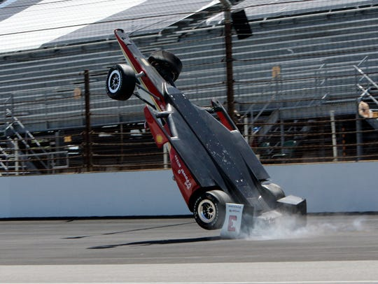 The car driven by Helio Castroneves flips after hitting