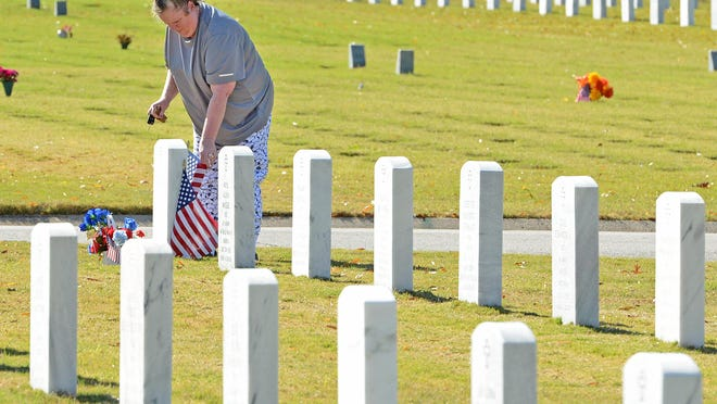 Dawn Plymale places a flag and flowers at her husband's (Tech Sgt. David T. Plymale) gravesite at the National Cemetery in Fort Smith on Veterans Day, Wednesday, Nov. 11. Tech Sgt. Plymale was in the Air Force during Vietnam and served for more than 20 years.