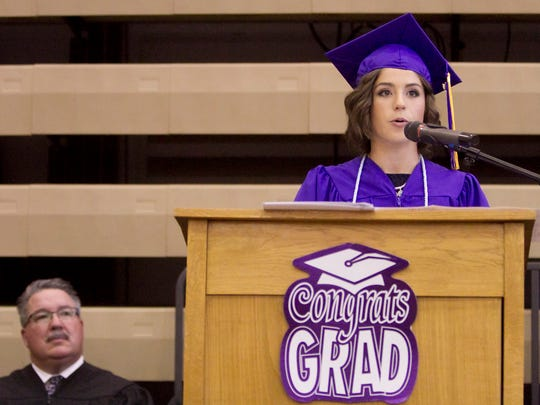 Emma Roedel, 2016 class co-president, addresses the class at Fowlerville's graduation as dad Wayne Roedel, Fowlerville Schools superintendent, listens.