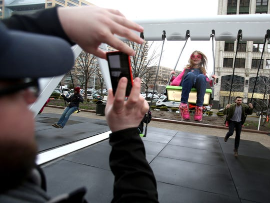 Jake Ireland, 30 of Romeo uses his iPhone to take pictures of his daughter Isibeal Ireland, 9, of Romeo during the first day that the interactive musical swing set was open to the public at Cadillac Square on Thursday, April 7, 2016.