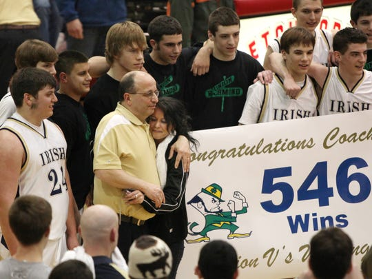 Batavia Notre Dame boys basketball coach Mike Rapone, (left in yellow shirt), is surrounded by family, friends and his players after his team defeated Arkport in their 2010 Section V Class D1 semifinal. He became the winningest coach in Section V boys basketball history on March 3 of that year.