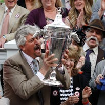 Trainer Steve Asmussen hoisted the trophy after Untapable won the Kentukcy Oaks at Churchill Downs. May 2, 2014