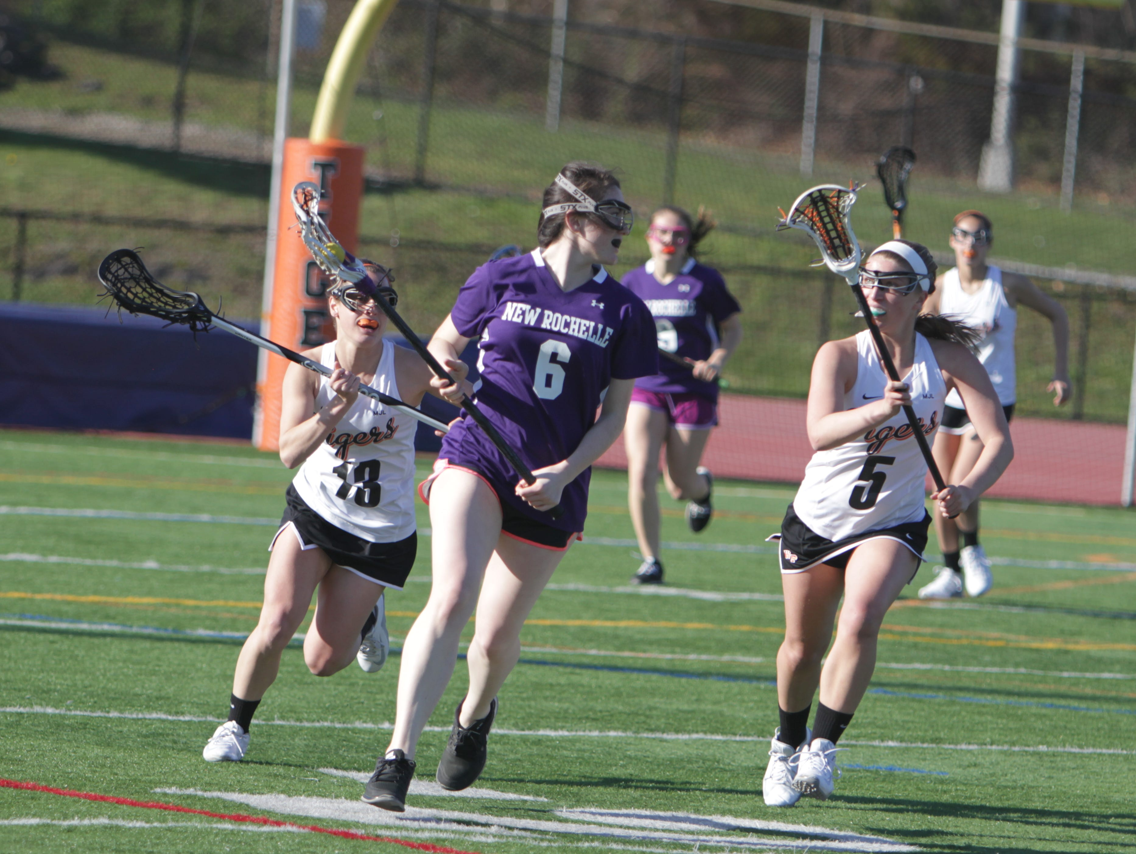 New Rochelle's Bella Dente is defended by White Plains' Amanda Broderick (13) and Katie Avezzano during a Section 1 girls lacrosse game between New Rochelle and White Plains at White Plains High School on Wednesday, April 13th, 2016. White Plains won 11-6.