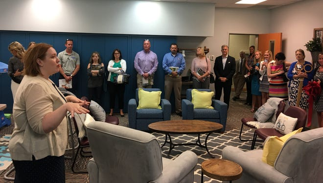 Amelia Clark, far left, shows the new furnishings in a room at the Suzanne Gresham Center where babies and mothers can receive help to overcome drug addiction. Clark is regional vice president  for Meridian Health Services.