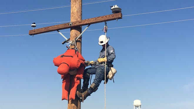 """APS lineman """"rescuing"""" 185 pound dummy at the work site where APS linemen train to quickly restore power after outages."""