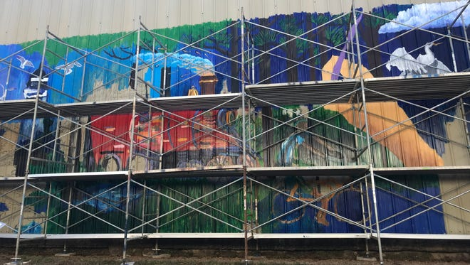 Just a few more strokes! The mural on the AMWAT building in its final development stages.