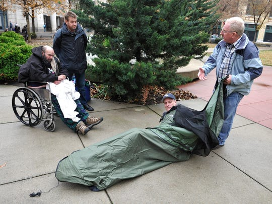 Steve Lindstrom and Bobby Jenkins show two homeless men, Tim Waggoner (wheelchair) and Bob Wilkins, how the Backpack Bed works.