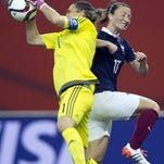 Germany goalkeeper Nadine Angerer (left) makes a save as France's Gaetane Thiney moves in during their quarterfinal match last Friday.
