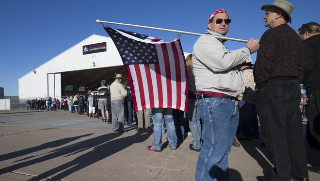Nohl Rosen of Phoenix holds a flag while waiting in line for a campaign rally for Republican presidential candidate Donald Trump at Phoenix-Mesa Gateway Airport on Wednesday.