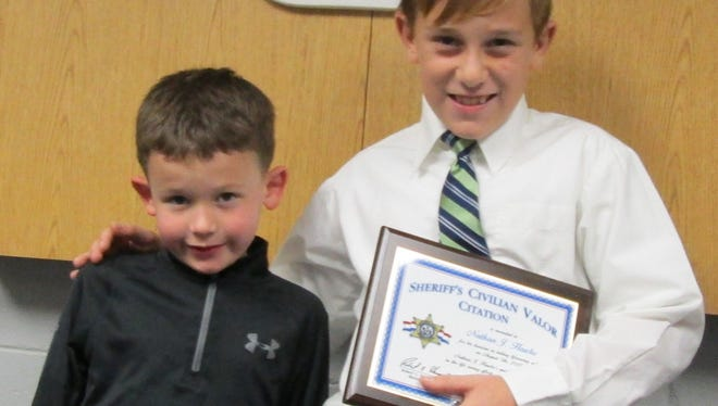 Ten-year-old Nathan Hawke (right), of Two Rivers, was recently honored by the Manitowoc County Sheriff's Office for his efforts in saving his 6-year-old cousin, Richard Vaillancourt (left), in August.