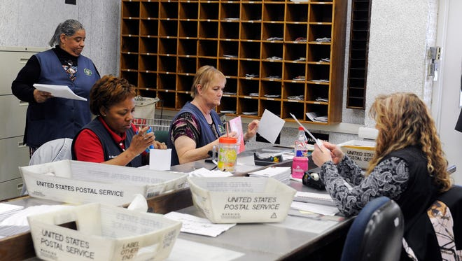 In this Feb. 5, 2016, photo, mail clerks at the Wynne Unit of the Texas prison system inspect boxes of letters for inmates in Huntsville, Texas. Every piece of mail is checked for contraband like drugs hidden under stamps or messages, or words in correspondence that suggest violence or escape plans, or attempts by convicts to profit from some enterprise or business while behind bars.