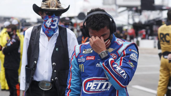 Driver Bubba Wallace, right, is overcome with emotion as he and team owner Richard Petty walk to his car in the pits of the Talladega Superspeedway prior to Monday' start.