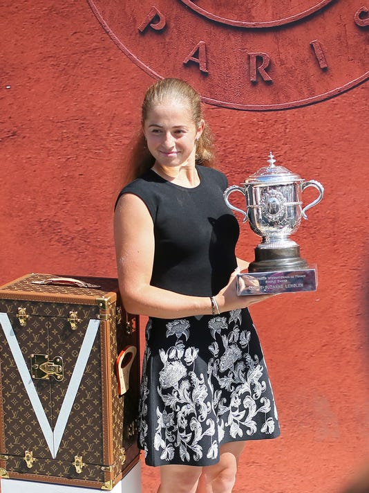 Latvia's Jelena Ostapenko holds the trophy during a photo call one day after winning the women's final match of the French Open tennis tournament against Romania's Simona Halep in three sets 4-6, 6-4, 6-3, at the Roland Garros stadium, in Paris, France, Sunday, June 11, 2017. (AP Photo/David Vincent)