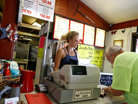 Carrie West rings up a customer June 25 at Spare Rib BBQ Co. in Farmington.