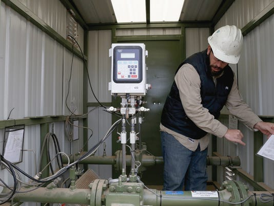 Dustin Porch, a production inspector for BLM, checks the gas temperature during an inspection at a ConocoPhillips oil well off on Light Plant Road in Aztec on Jan. 29.