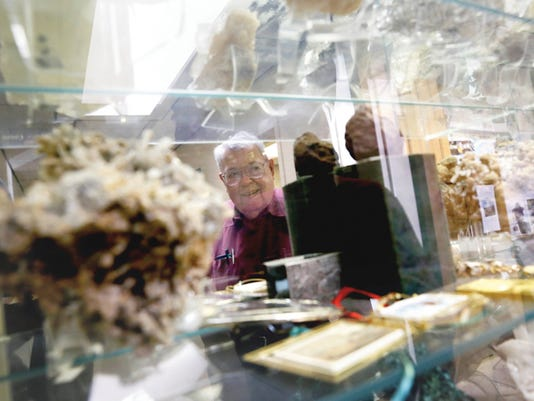 Tom Dugan looks over his mineral collection on Feb. 4 at Dugan Production Corp. in Farmington.