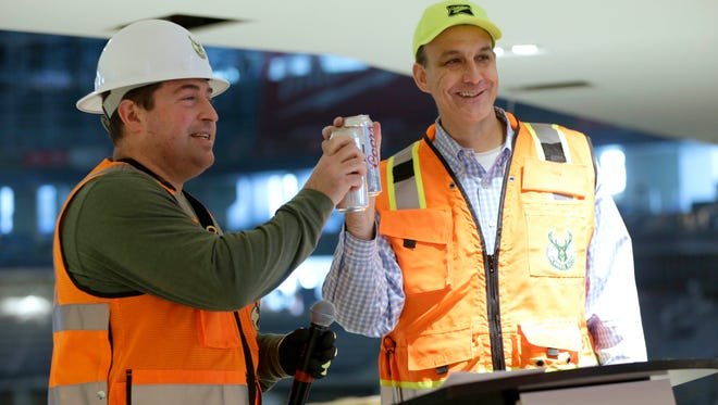 Milwaukee Bucks President Peter Feigin and Jim Kanter, Miller Brewing general manager for Wisconsin, toast with a can of Miller and a can of Coors Light at the end of the partnership announcement Thursday.