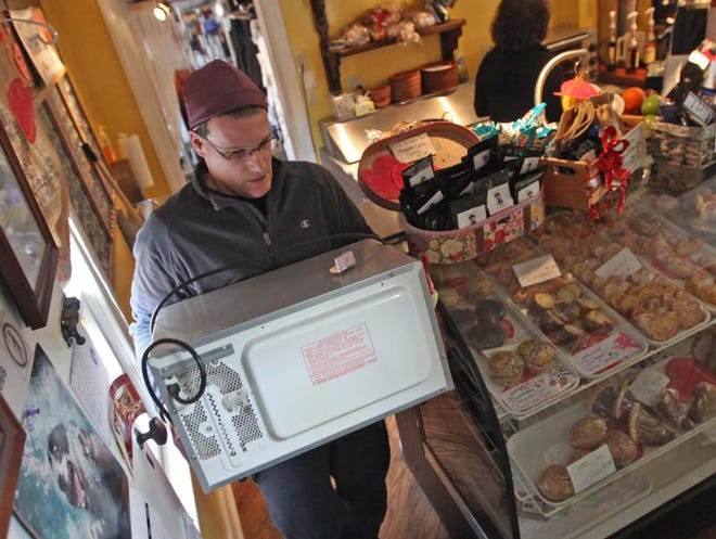 After discovering an underground pipe was leaking beneath Esther and Matthew Lovlie's business Penn's Place, a coffee shop in New Castle, Matthew carries a microwave out of the way on Monday so repairs can begin.