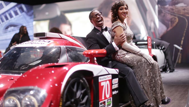 Jerald Davis of Sterling Heights and his wife Pamela Davis of Sterling Heights pose for a photo on a Mazda Prototype race car during the 2016 North American International Auto Show Charity Preview at Cobo Center on Friday, Jan. 15, 2016, in Detroit.