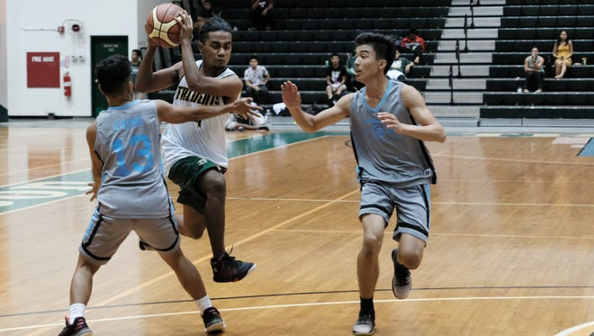 A UOG Trident player makes his move to the basket in traffic against GCC in their game Tuesday night at the University of Guam Calvo Field House.