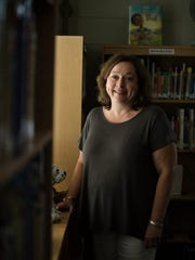 Principal Kathi Atkins stands in the library room inside