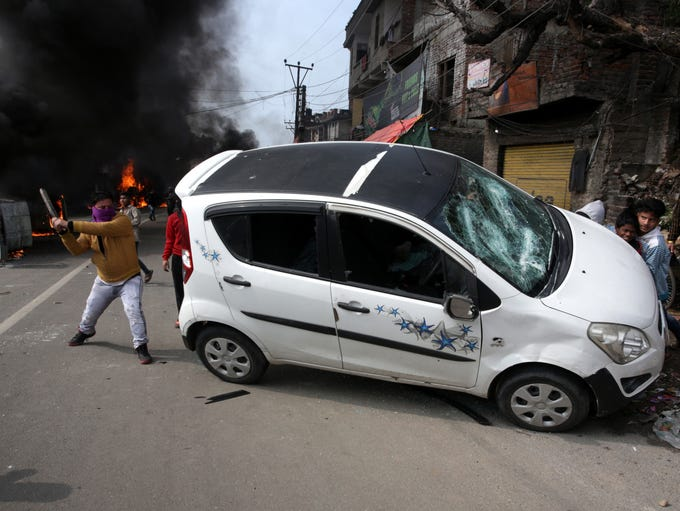 Indian protesters damage vehicles during a protest