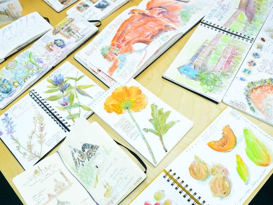 Sketch books by Rosemary Connelly lay out on the table