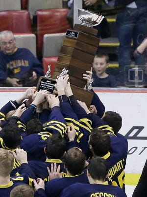 Michigan hockey players hold the MacInnes Cup after defeating Michigan Tech 4-2 in the championship game of the Great Lakes Invitational NCAA college tournament, Wednesday, Dec. 30, 2015, in Detroit.
