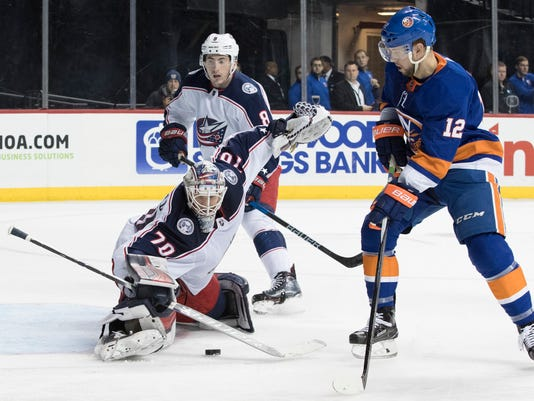 Columbus Blue Jackets goaltender Joonas Korpisalo (70) blocks a shot by New York Islanders right wing Josh Bailey (12) during the second period of an NHL hockey game, Saturday, Feb. 3, 2018 in New York. (AP Photo/Mary Altaffer)