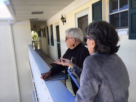 Sandy Warnke, president of the Stratford Place Home Owners Association and resident Kathy Kozulinski eye proposed site of 7-Eleven gas station from the balcony of their building a few hundred feet away.