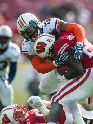 Auburn linebacker Kris Frost (17) tackles Wisconsin running back Melvin Gordon (25) during the Outback Bowl between Auburn and Wisconsin at Raymond James Stadium in Tampa, Fla., on Thursday, Jan. 1, 2015. Wisconsin defeated Auburn 34-31.