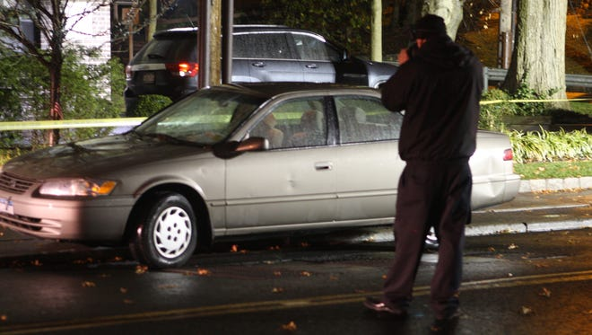 A Greenburgh police investigator photographs a car that struck a 27-year-old woman on East Hartsdale Avenue.
