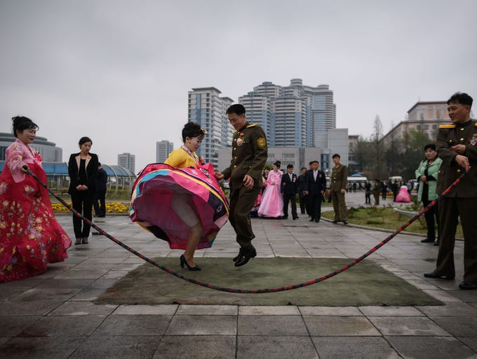 A bride and groom jump over a skipping rope as they