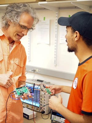 New Mexico State University Electrical and Computer Engineering Associate Professor Paul Furth, left, and graduate student Abdelrahman Elkanishy discuss a Bluetooth wireless communications integrated circuit used to measure the rate at which a computer chip consumes and transmits power.