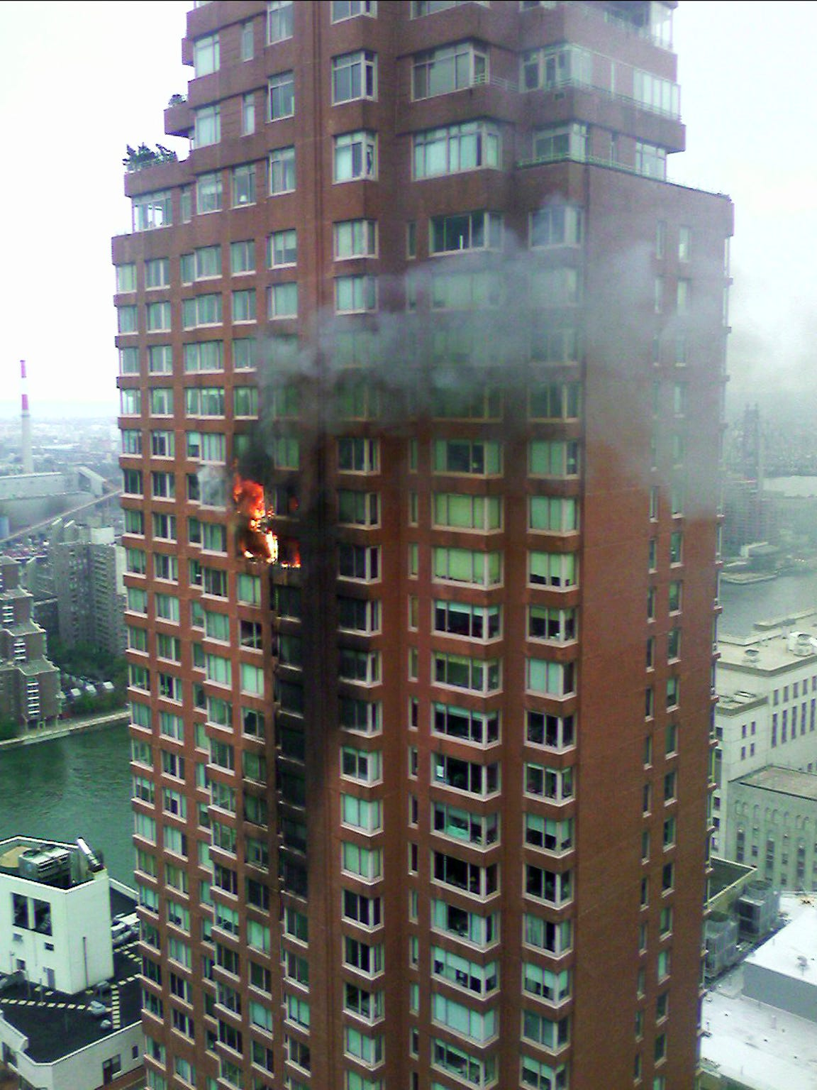 Flames and smoke are seen coming out of windows at the location where a small plane crashed into a 50-story residential apartment building near 71st Street and York Avenue in New York. The crash killed New York Yankees pitcher Cory Lidle.