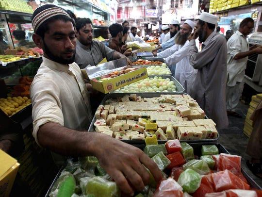 Pakistani men buy sweets ahead of the Muslim festival