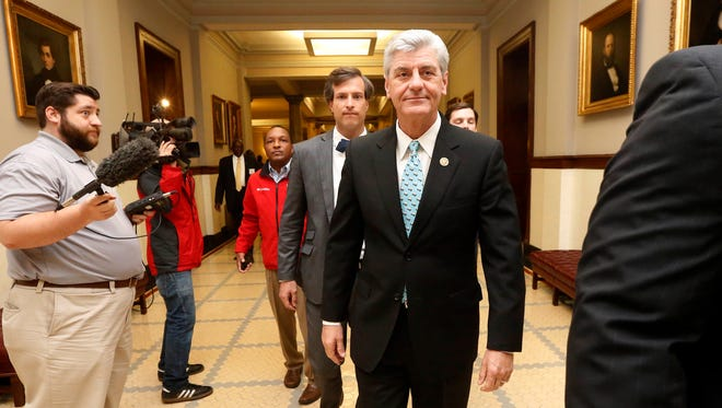 Republican Gov. Phil Bryant, right, walks past reporters on his way to a meeting of a youth jobs program board at the Capitol in Jackson.