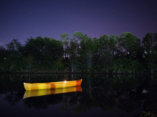 A canoe with a single lit candle floated nearby where
