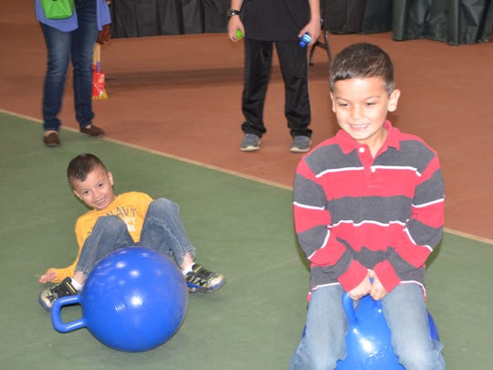 Logan, right, and Lucas Garza, use the bouncing medicine balls during Saturday's Health Kids Day at the Sandusky County YMCA.