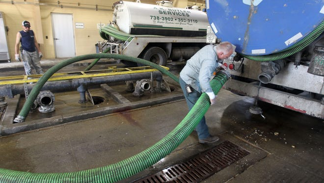 Darryl Fields, of Savings Liquid Waste, attaches a hose to drain his tanker truck, which is used to clean out septic systems,  at the Metropolitan Sewer District plant in Lower Price Hill.  In the background is Jeremy Moses, of A.K. Butler Services, who was also emptying his truck.