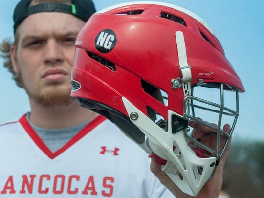 Austin Fairchild, a senior member of the Rancocas Valley boys' lacrosse team, who lost his friend and teammate Nicky Green to suicide in 2012, displays his helmet with Green's initials on it, prior to a boys' lacrosse game on Thursday. The group of Rancocas Valley seniors who starting playing lacrosse with Nicky in middle school have dedicated their final season together to Green, the one who brought them all together. 04.02.15