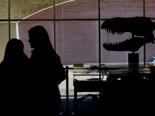 Students walk past a T-Rex skull replica at the Nasr Natural Science Museum in the Clara E. Mackenzie building on the campus of St. Clair County Community College in Port Huron.